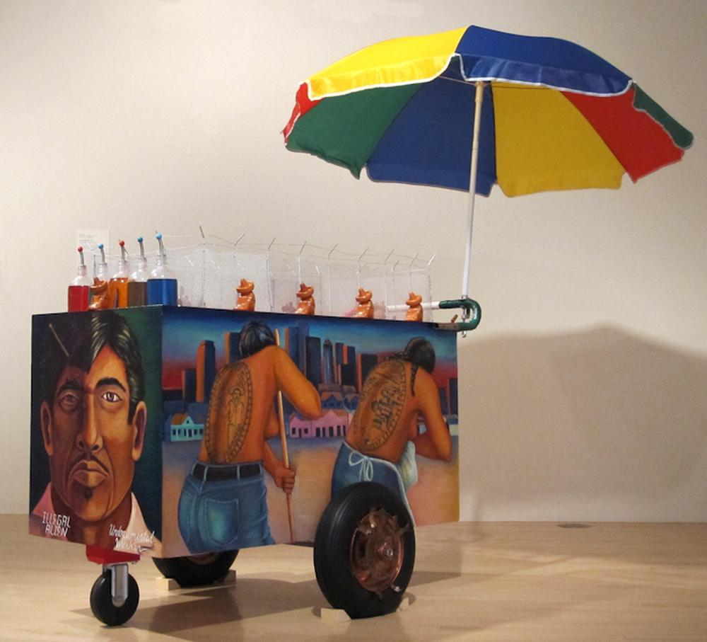 Installation image of a vendor cart painted and staged in a gallery space