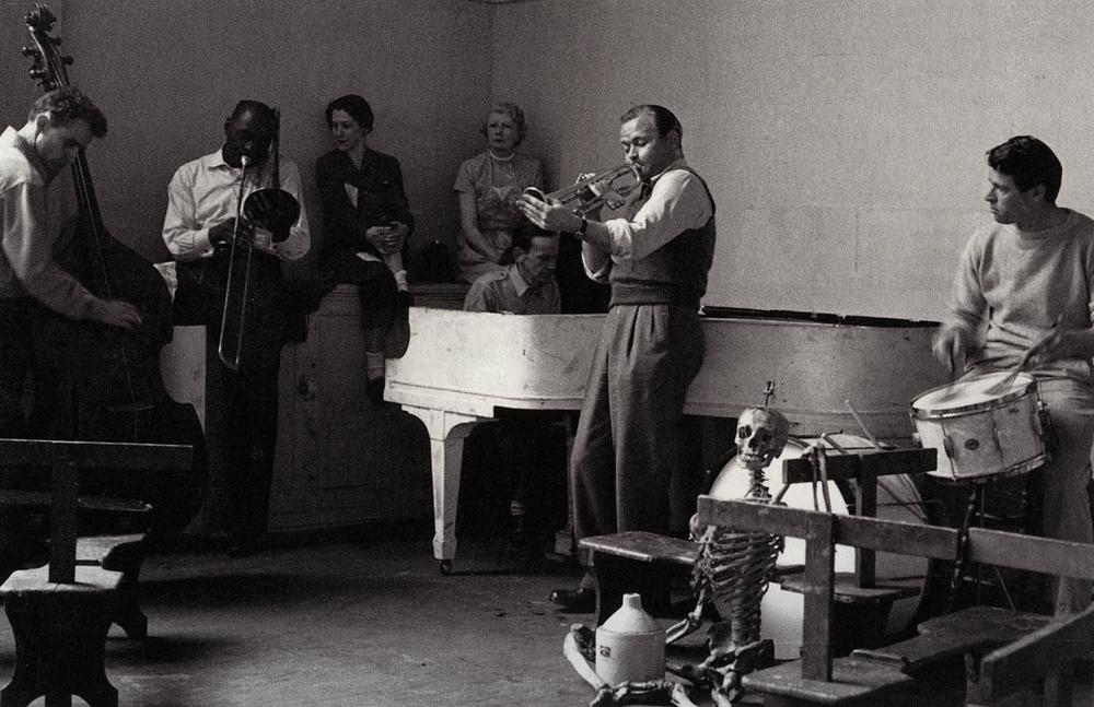 jazz band musicians playing music in open room with onlookers sitting amongst them