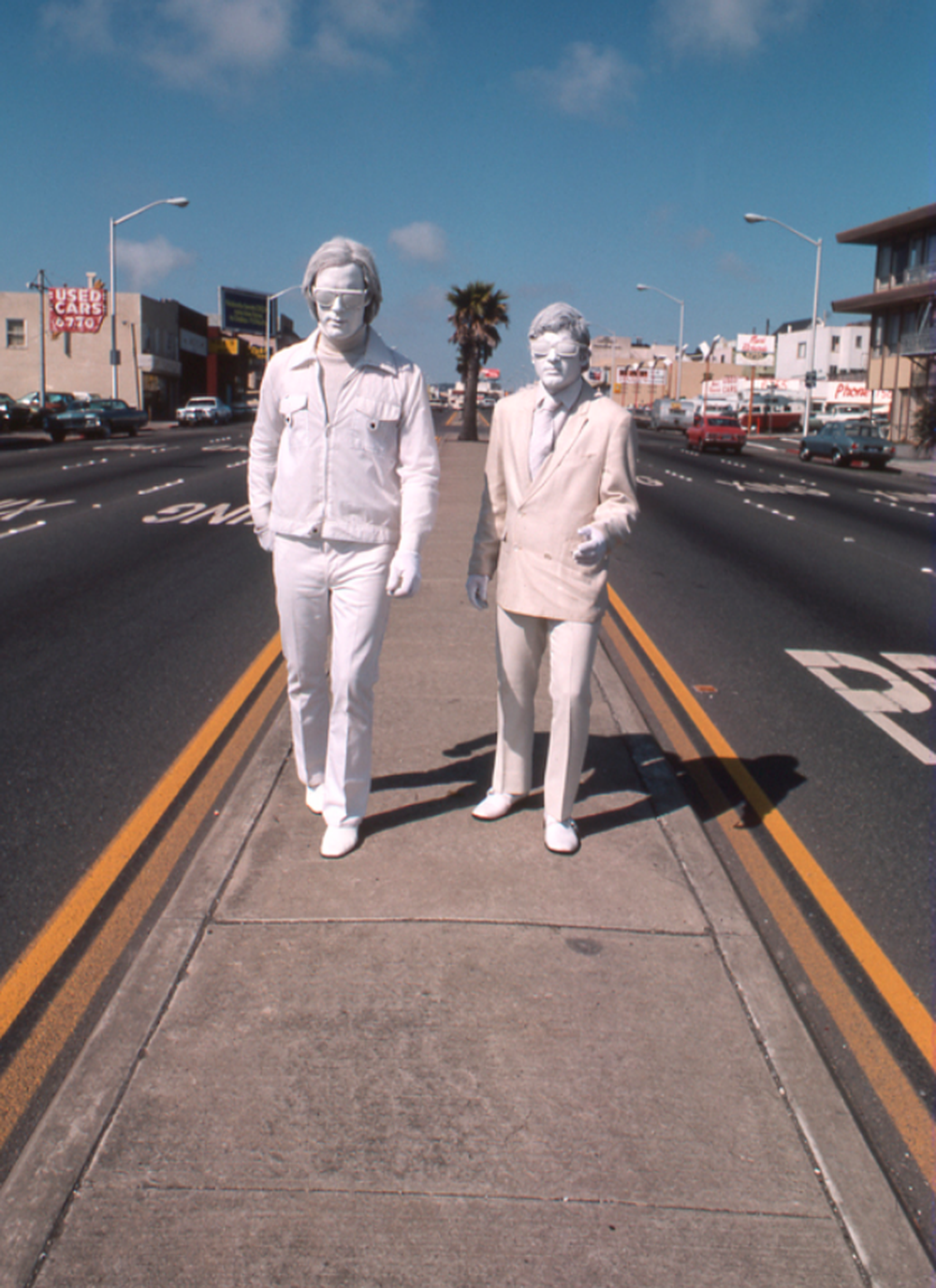 two men painted white wearing white clothing on the medium of a busy street
