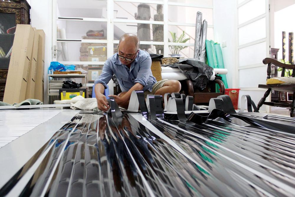asian man working on floor with long photographic strips