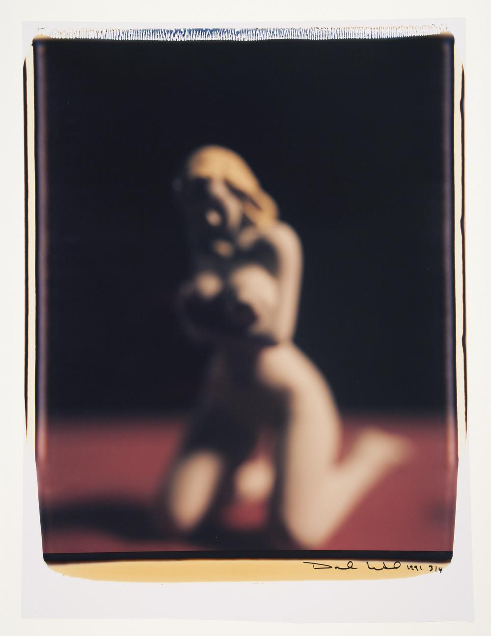 blurry image of nude blonde woman kneeling and facing the viewer while trying to cover herself