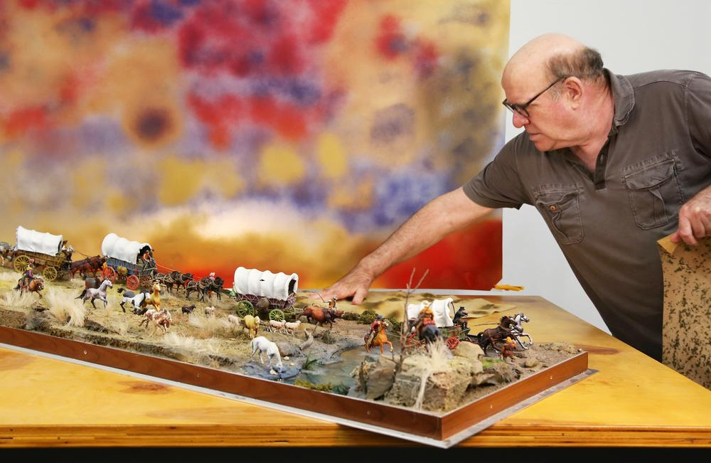 white man leaning over a diorama