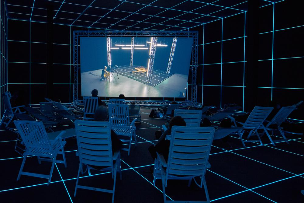 projection screen in a gallery with chairs for viewers in a darkened room with blue illumination