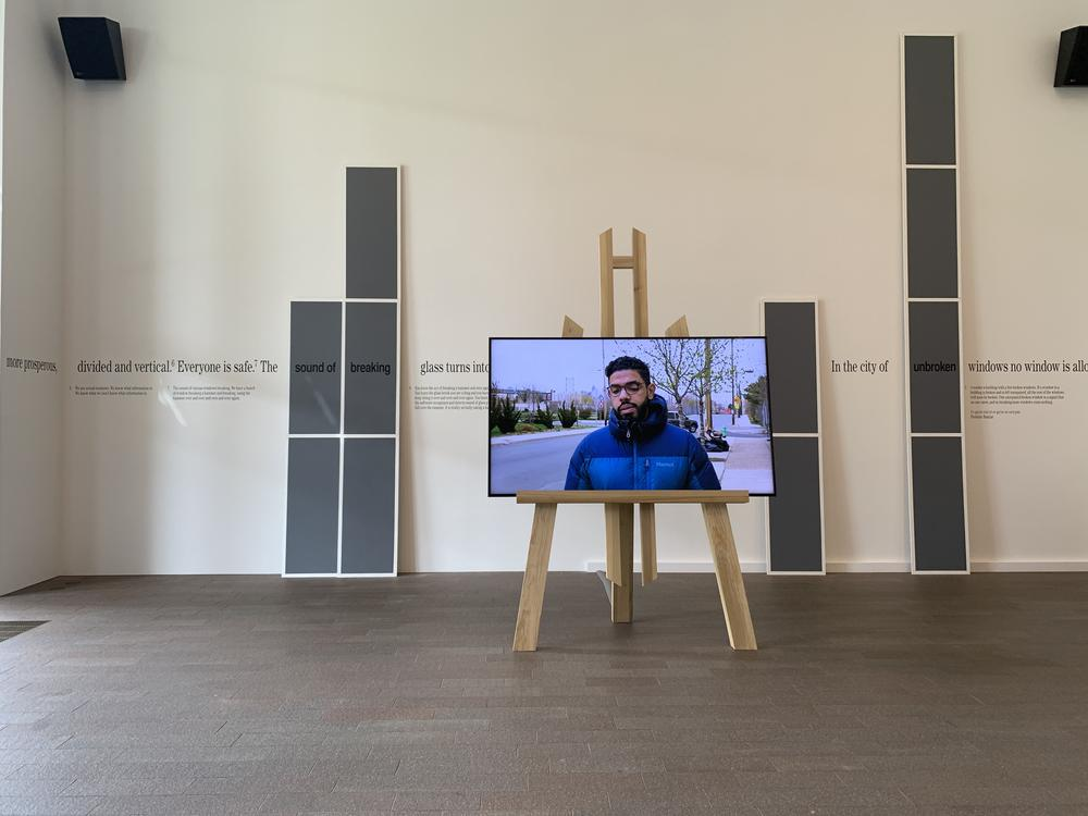 tv monitor with video displayed on easel in a gallery of works