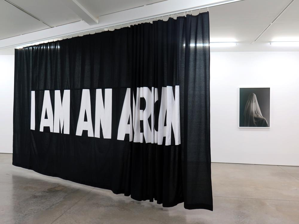 A large black fabric banner with white type face that says I am an and the last word is not clearly written out