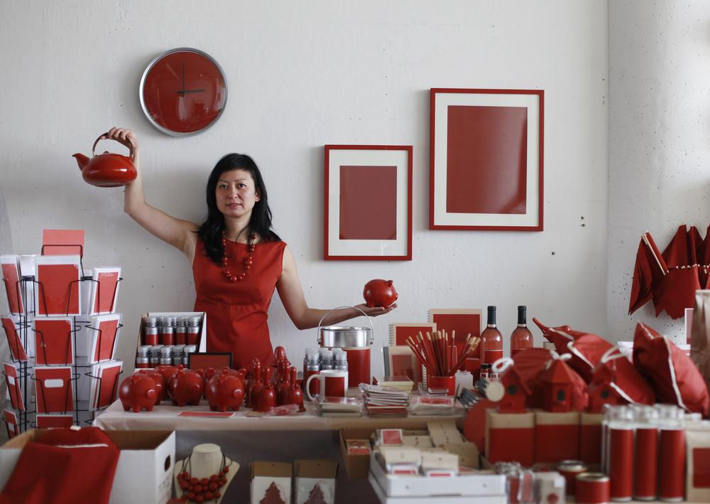 artist holding products from her red colored store and collateral