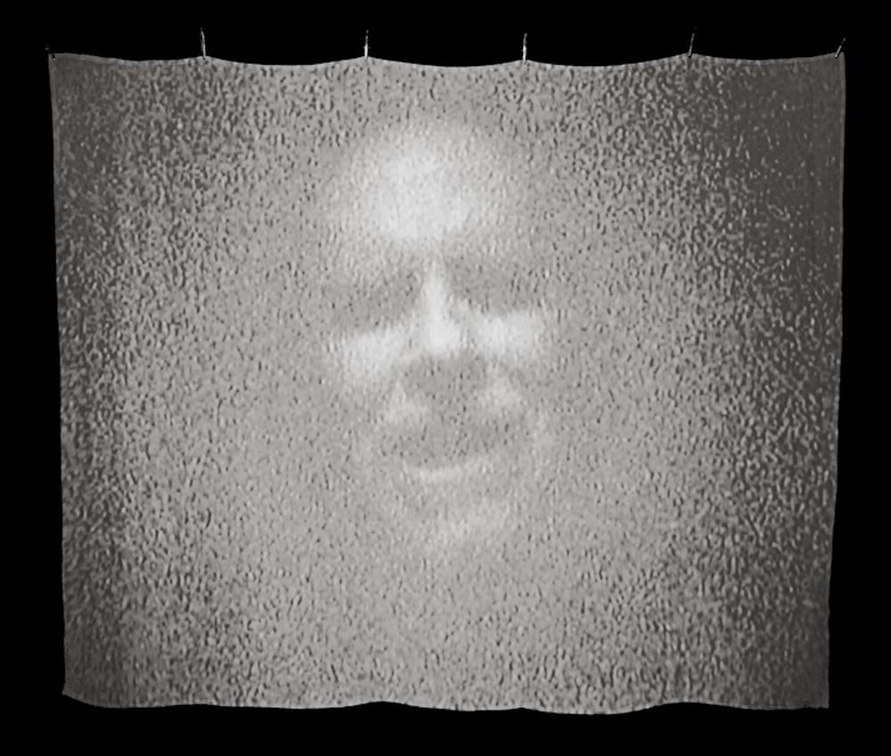 ghostlike image of a face projected on a silk screen